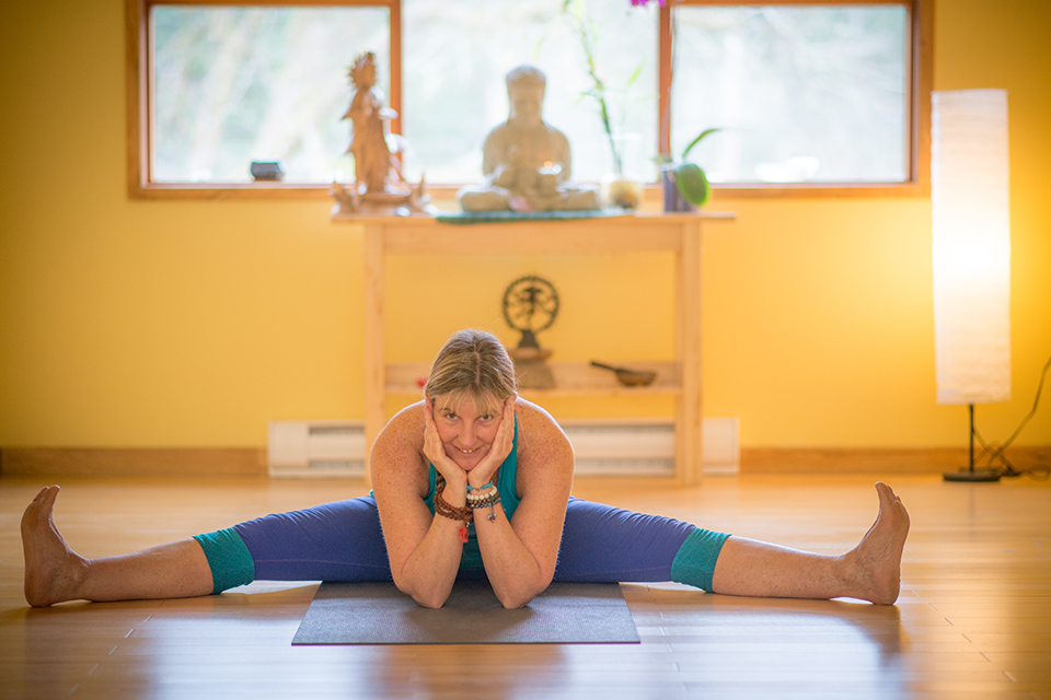 A woman in a wide legged forward bend yoga pose